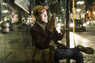 Portrait of young man on the phone sitting at bus stop by night, Lisbon, Portugal - UUF19177