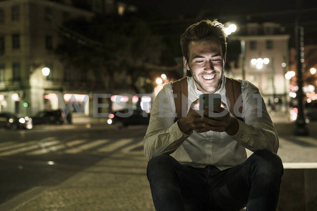 Portrait of happy young man using cell phone in the city by night, Lisbon, Portugal - UUF19186 - Uwe Umstätter/Westend61