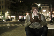 Portrait of happy young man using cell phone in the city by night, Lisbon, Portugal - UUF19186