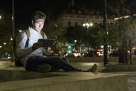 Portrait of young man using digital tablet and earphones in the city by night, Lisbon, Portugal - UUF19189