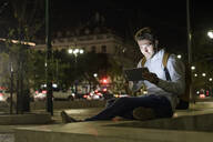 Portrait of young man using digital tablet and earphones in the city by night, Lisbon, Portugal - UUF19192