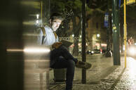 Portrait of young man waiting at bus stop by night using digital tablet and earphones, Lisbon, Portugal - UUF19195