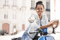 Smiling young woman with motor scooter and mobile phone in the city, Lisbon, Portugal - UUF19204