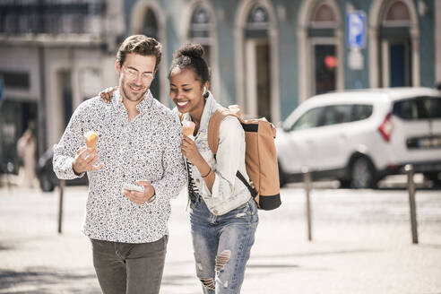 Happy young couple with ice cream and mobile phone in the city on the go, Lisbon, Portugal - UUF19216
