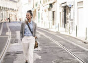 Smiling young woman with wireless earphones in the city on the go, Lisbon, Portugal - UUF19228