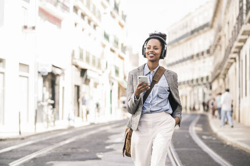 Smiling young woman with headphones and mobile phone in the city on the go, Lisbon, Portugal - UUF19234