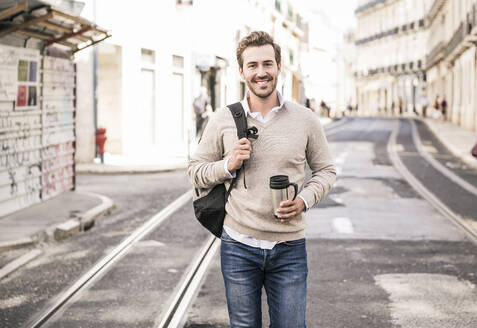 Portrait of smiling young man with backpack and coffee mug in the city on the go, Lisbon, Portugal - UUF19240