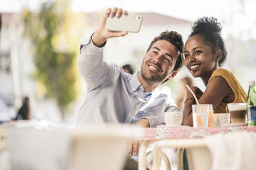 Happy young couple taking a selfie at an outdoor cafe - UUF19249