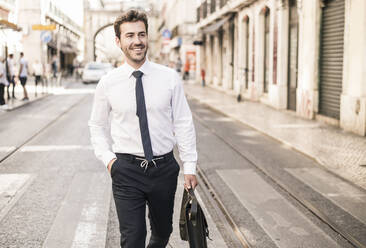 Smiling young businessman in the city on the go, Lisbon, Portugal - UUF19255