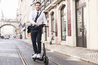 Young businessman riding e-scooter in the city, Lisbon, Portugal - UUF19258
