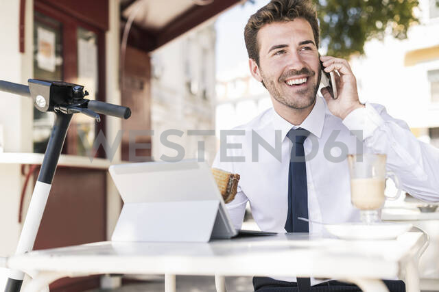 Happy young businessman on the phone at a cafe in the city, Lisbon, Portugal - UUF19270 - Uwe Umstätter/Westend61