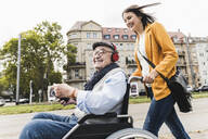 Laughing young woman pushing happy senior man with headphones and smartphone in wheelchair - UUF19273