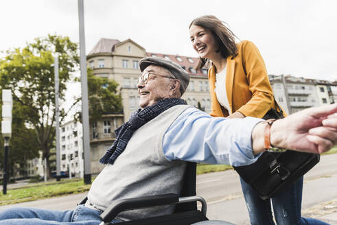 Laughing young woman pushing happy senior man in wheelchair - UUF19276