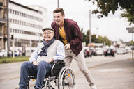 Laughing young man pushing happy senior man in wheelchair - UUF19288