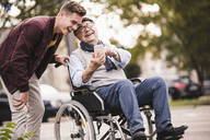 Laughing senior man in wheelchair and his adult grandson looking together at smartphone having fun - UUF19291
