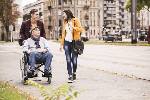 Senior man in wheelchair spending time with his grandchildren - UUF19294
