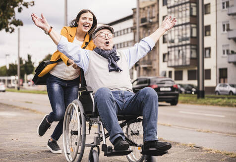 Portrait of young woman pushing senior man in wheelchair on pavement - UUF19300