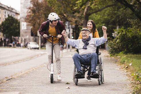 Senior man in wheelchair having fun with his adult grandchildren outdoors - UUF19303