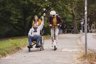 Senior man in wheelchair having fun with his adult grandchildren outdoors - UUF19306