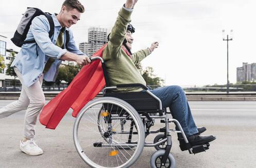 Young man pushing senior man sitting in a wheelchair dressed up as superhero - UUF19315