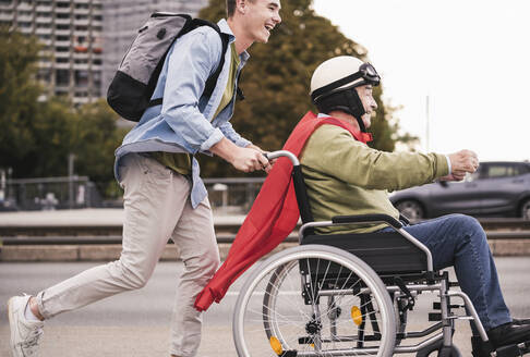 Young man pushing senior man sitting in a wheelchair dressed up as superhero - UUF19318