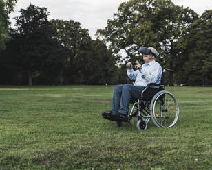 Senior man sitting in wheelchair in a park using Virtual Reality Glasses - UUF19351