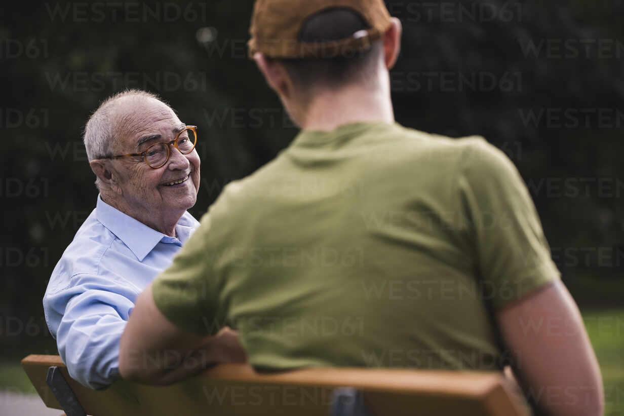 Portrait of smiling senior man relaxing together with his grandson on a park bench - UUF19360 - Uwe Umstätter/Westend61