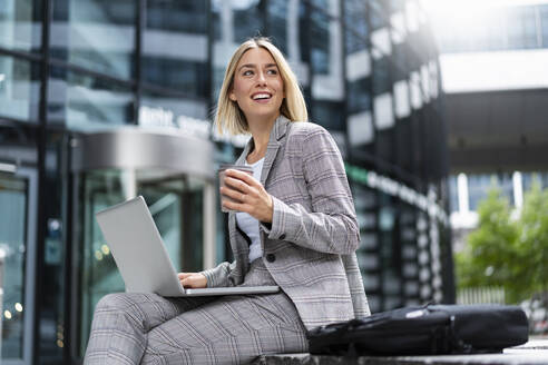 Smiling young businesswoman using laptop in the city - DIGF08638