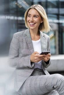 Happy young businesswoman with mobile phone in the city - DIGF08647