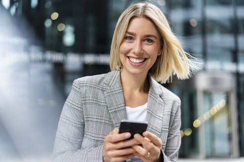 Portrait of happy young businesswoman with mobile phone in the city - DIGF08650