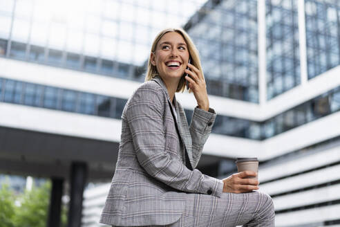 Happy young businesswoman on the phone in the city - DIGF08653