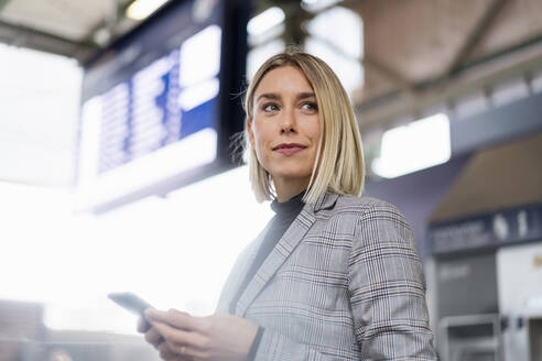 Young businesswoman with mobile phone at the train station - DIGF08659