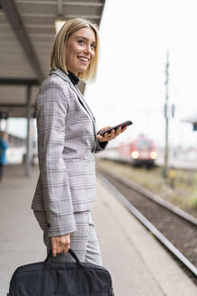 Smiling young businesswoman with mobile phone at the train station - DIGF08662