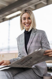 Portrait of smiling young businesswoman with newspaper at the train station - DIGF08665