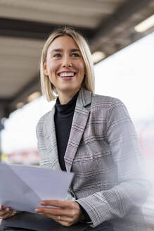 Happy young businesswoman with papers at the train station - DIGF08668