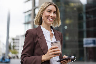 Happy young businesswoman in the city on the go - DIGF08692