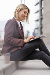 Smiling young businesswoman using tablet in the city - DIGF08695