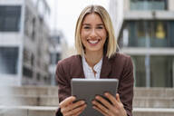Portrait of happy young businesswoman using tablet in the city - DIGF08698