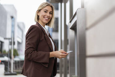 Portrait of smiling young businesswoman withdrawing money at an ATM in the city - DIGF08704