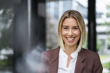 Portrait of happy young businesswoman in the city - DIGF08707