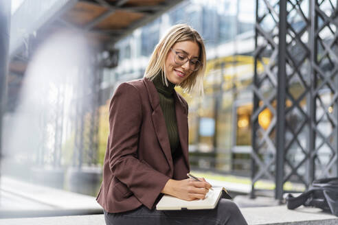 Smiling young businesswoman taking notes in the city - DIGF08710