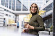 Happy young woman with takeaway coffee in the city - DIGF08716