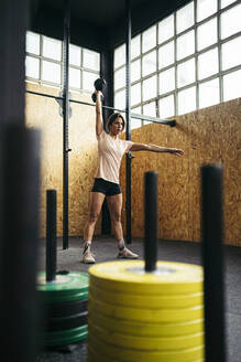Young woman doing dumbbell exercise at gym - MTBF00071