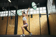 Young woman doing overhead squat exercise at gym - MTBF00077