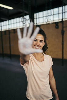 Happy sportswoman showing her hand with magnesium during cross training - MTBF00080