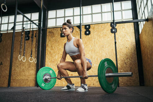 Young woman doing overhead squat exercise at gym - MTBF00083