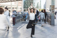 Young businesswoman practising yoga in the city at rush hour, Berlin, Germany - WPEF02182