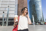 Smiling young businesswoman with takeaway coffee on the phone in the city, Berlin, Germany - WPEF02185
