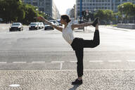 Young businesswoman practising yoga in the city, Berlin, Germany - WPEF02188