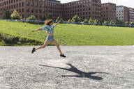 Young woman jumping and running in the city in summer - WPEF02200